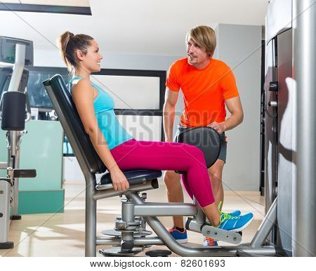 Hip abduction woman exercise at gym indoor closing legs and personal trainer blond man