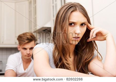 Unhappy couple having an argument in the kitchen at home.