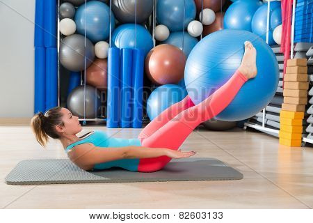 Ab exercise woman swiss ball leg lifts Pilates workout abs at gym