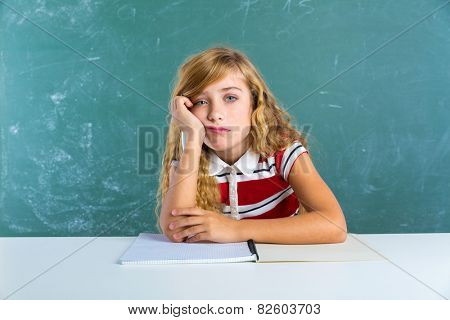 Boring sad expression student schoolgirl on classroom desk at school green chalk board