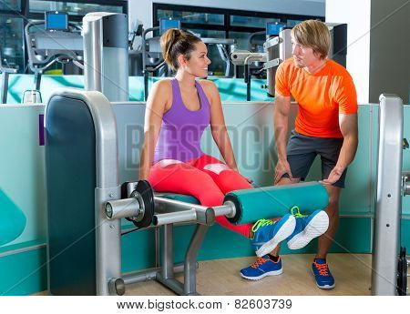 Gym leg extension exercise workout woman with blond personal trainer man