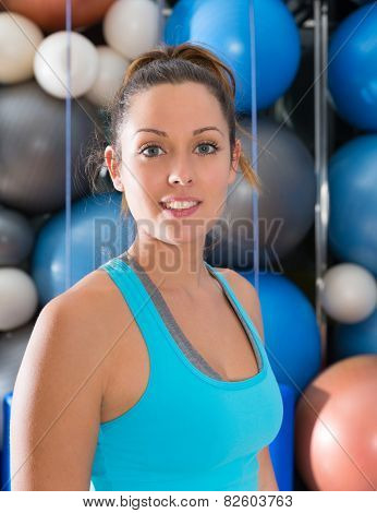 Blue eyes beautiful woman smiling at gym portrait with swiss and pilates yoga balls background