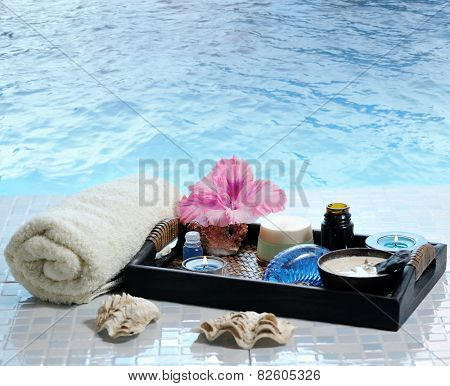 toiletries with flower and candles on a tray near the sea