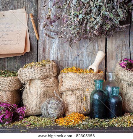 Healing Herbs In Hessian Bags, Bottles Of Tincture And Paper Sheet With  Recipes On Wooden Wall Back