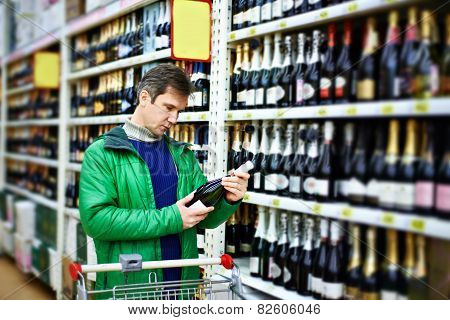 Man Choosing Wine In Supermarket