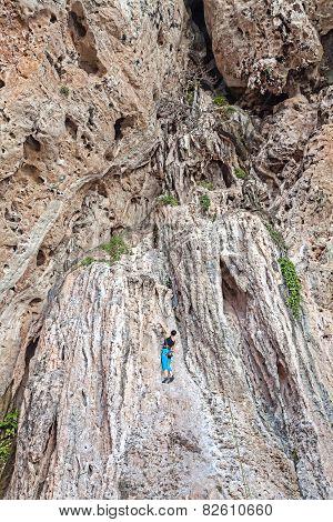 Woman Climbing Incredible Wall, Railay Beach In Thailand.