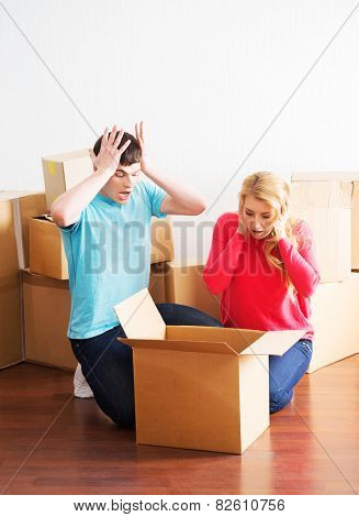 Young couple moving in a new home. Man and woman unboxing fragile stuff. Negative emotions.