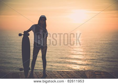 Beautiful fashion skater girl posing with  a skateboard at the sunset