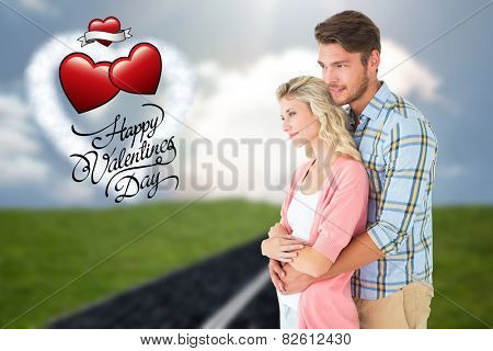Attractive couple embracing and smiling against road on grass