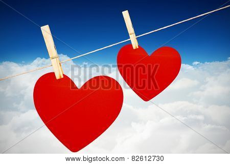 Hearts hanging on a line against bright blue sky over clouds