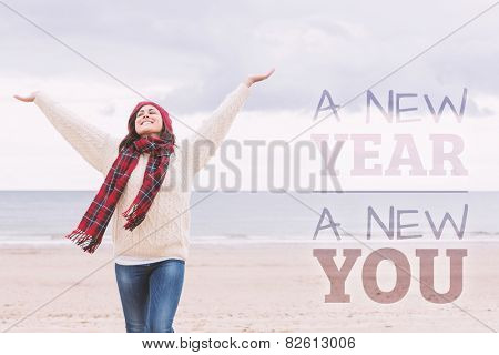 Woman in warm clothing stretching arms on beach against new year new you