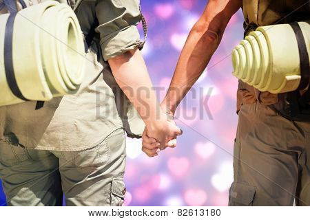 Hitch hiking couple standing holding hands on the road against valentines heart pattern