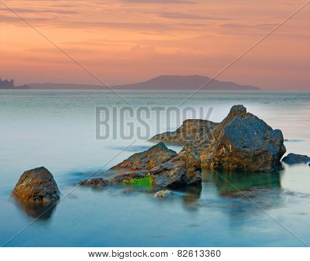 Nice evening scene with stones in water on sea