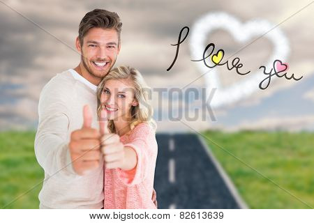 Attractive couple showing thumbs up to camera against road on grass