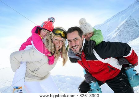 Parents giving piggyback ride to kids in snowy mountains