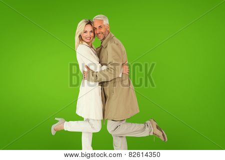 Happy couple posing in trench coats against green vignette