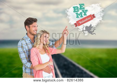 Attractive young couple embracing and pointing against cloud heart