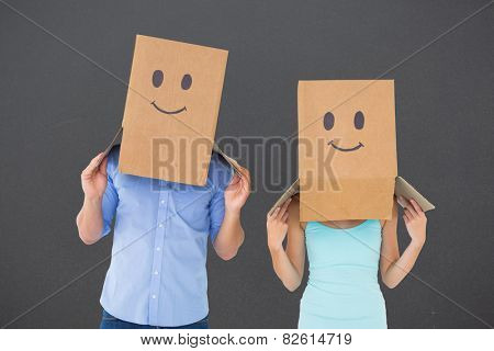 Couple wearing emoticon face boxes on their heads against grey