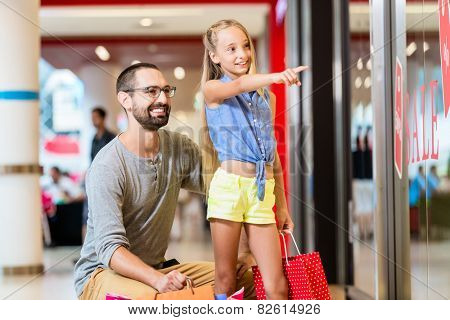 Family at shop window in mall shopping