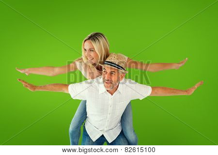 Happy man giving his partner a piggy back against green vignette