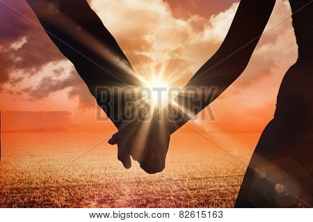 Mid section of newlywed couple holding hands in park against sunrise over field