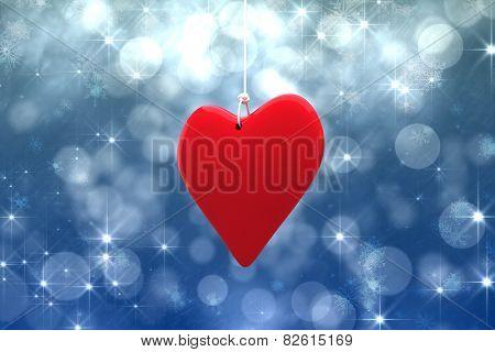 Red heart against shimmering light design on blue