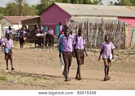 TORIT, SOUTH SUDAN-FEBRUARY 20, 2013: Unidentified students in uniform leave school in South Sudan.