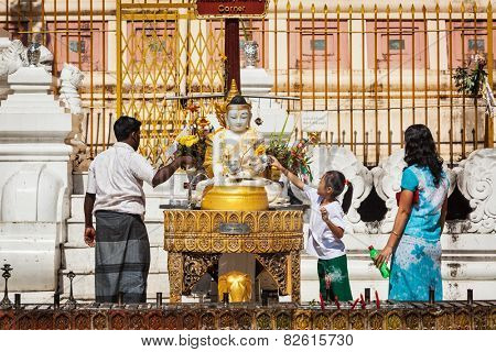 YANGON, MYANMAR - JANUARY 3, 2014: Myanmar family worshipping Buddha in  in Shwedagon Paya pagoda - the most sacred Buddhist pagoda in Myanmar