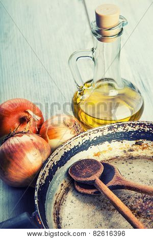 Old kitchen pan wooden spoon three onions carafe with olive oil on wooden table.