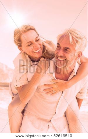 Man giving his smiling wife a piggy back at the beach on a sunny day