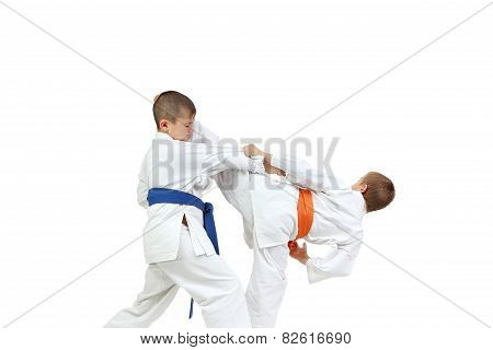 Sportsmen are doing paired exercises karate  on a white background