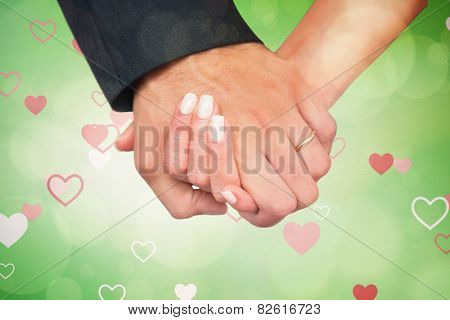 Newlyweds holding hands close up against love heart pattern