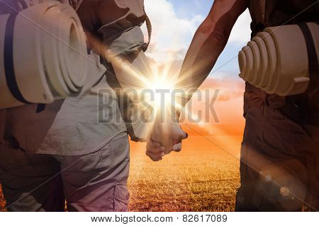 Hitch hiking couple standing holding hands on the road against sunrise over field