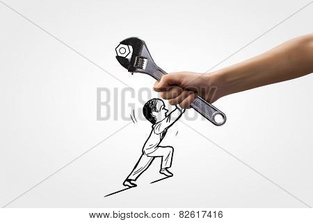 Human hand and caricature of man trying to move wrench