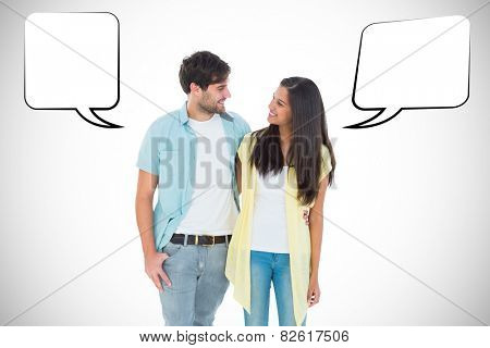 Happy casual couple smiling at each other against white background with vignette