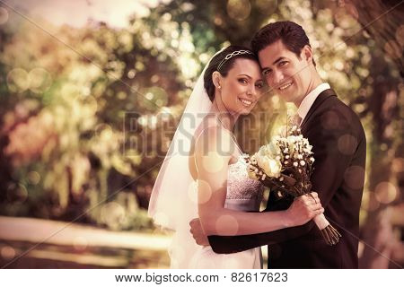 Portrait of loving newly wed couple with head to head standing in garden
