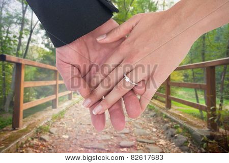 Close-up of bride and groom with hands together against bridge with railings leading towards forest