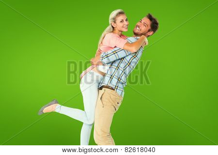 Handsome man picking up and hugging his girlfriend against green vignette
