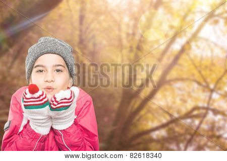 Wrapped up little girl blowing over hands against tranquil autumn scene in forest