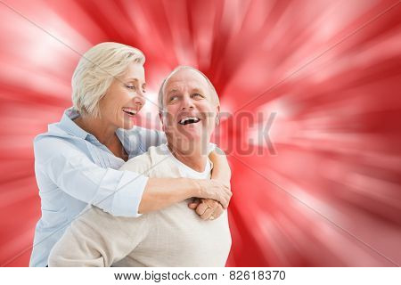 Happy mature couple smiling at each other against digitally generated twinkling light design