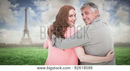 Casual couple standing arms around against eiffel tower