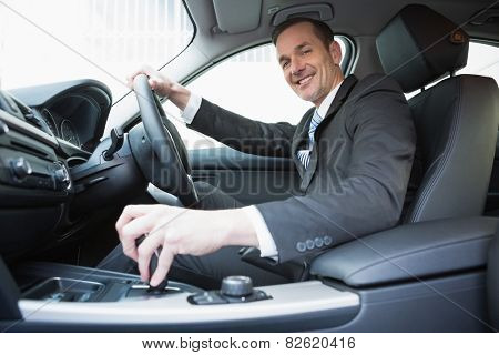 Smiling businessman in the drivers seat in his car