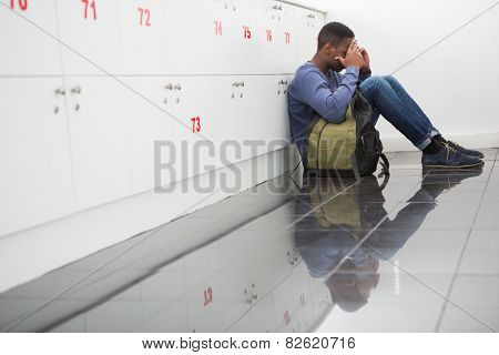 University student sitting alone with his hands on face at the university
