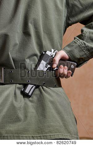 Soldier In Uniform Holding Gun In His Belt