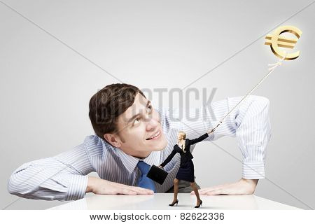 Young businessman and businesswoman pulling euro symbol on rope