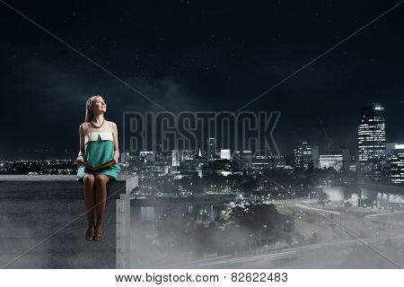 Young pretty girl sitting on building top with book
