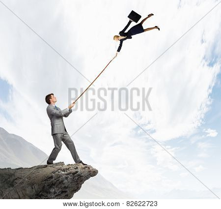 Businessman holding on lead young colleague businesswoman