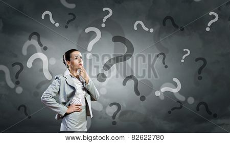 Portrait of pretty young businesswoman and many question marks around