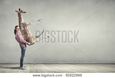 Funny young girl making effort to carry deer