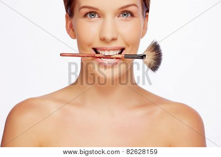 Attractive girl with powder brush between her teeth